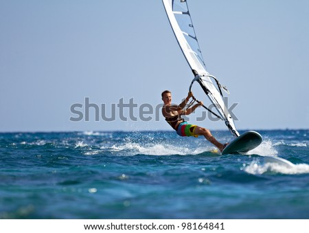 young man surfing the wind on a