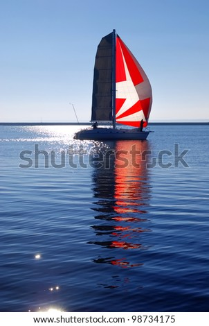 white yacht with red sail