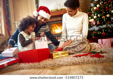 afro American parents looking in their little girl which opens Christmas presents