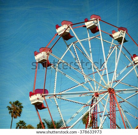 aged and worn vintage photo of ferris wheel with palm trees.