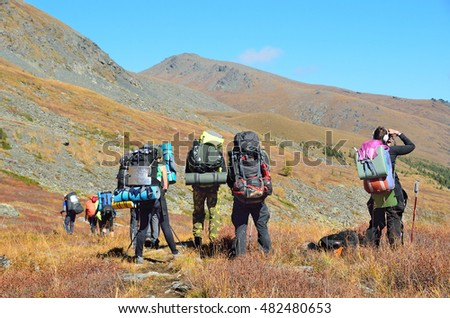 Altai territory, Ust-Koksinsky district, Russia, September, 09, 2016. tourists with backpacks walking along the riverbed of Acchan (Akchan) in september