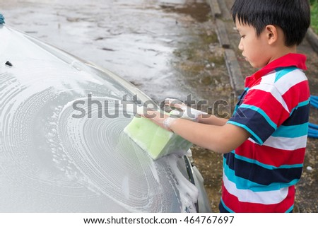 Asian boy with sponge over the car for washing.