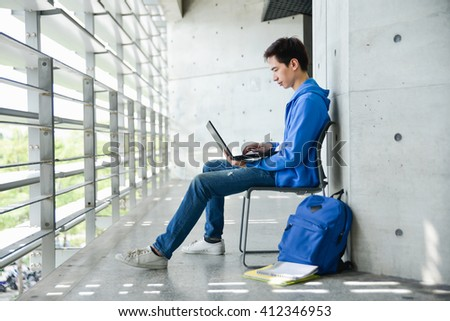 asian college student sitting student with laptop on campus