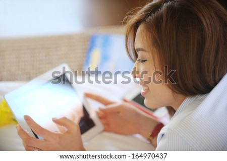 Asian teenage laughing while look at Ipad