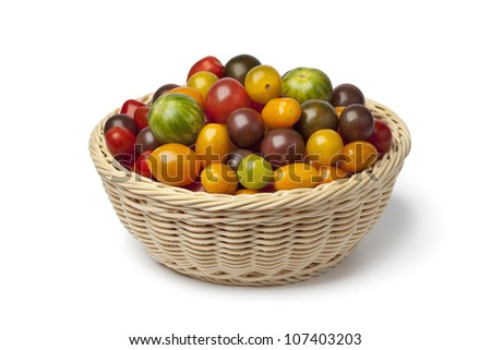 Basket with different color homegrown organic tomatoes on white background