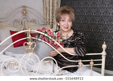 Beautiful woman aged with a bouquet of flowers in the bedroom