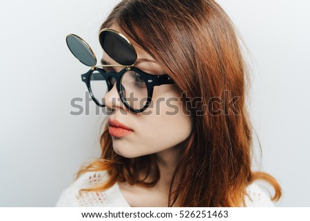 Beauty woman in fashion round glasses on a light background is not looking at the camera. fashion model.