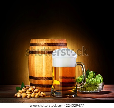 Beer barrel with beer glass on a wooden table. The dark background.