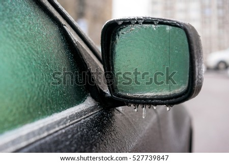 Black car coated ice crust during the  icy rain in cold weather. Side mirror and windows are covered  with ice after freezing rain