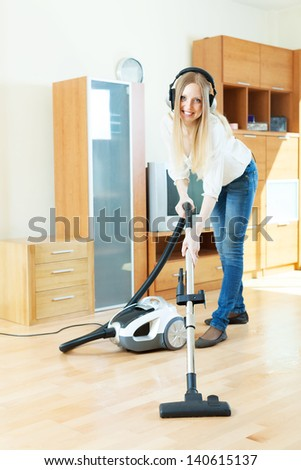 blonde woman in headphones cleaning with vacuum cleaner on parquet floor