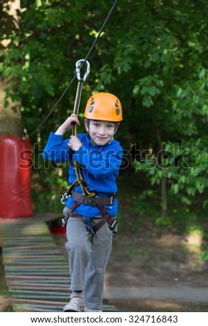boy climbing in adventure park , rope park