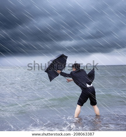 business man holding a umbrella to resist rainstorm