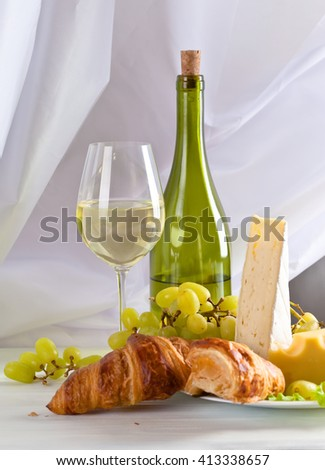 cheese with grapes and croissants on white table
