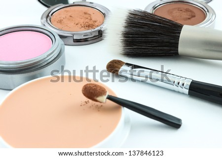 Cosmetics and brushes on white background