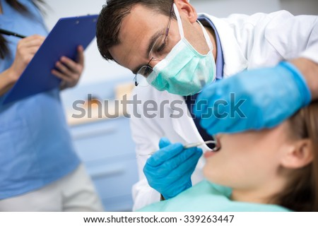 Dentist very  carefully  check up and repair tooth of his young female patient