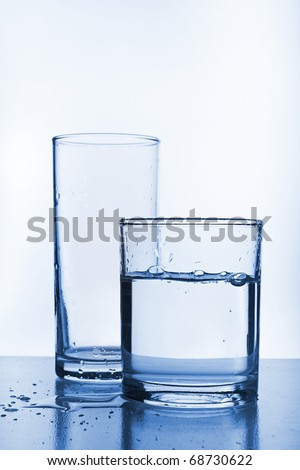 Empty glass behind full glass of water. Image stylized in blue tone  for more cool feeling