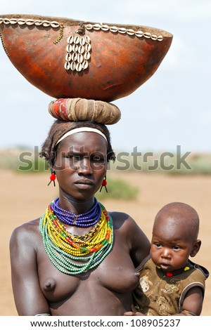ETHIOPIA - AUG 15:  Women of ethnic Erbore with her child,the ethnic groups in the The Omo valley Could disappear Because of Gibe III hydroelectric dam. on Aug 15, 2011 in Omo Valley, Ethiopia.