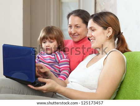 Family of three generations sits on the sofa with laptop
