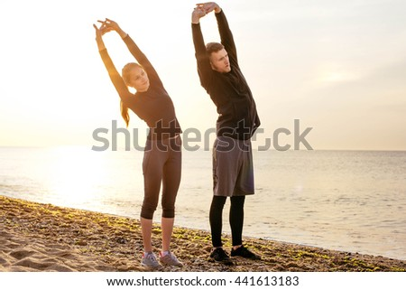 Fit young fitness couple working out on beach during sunrise or sunset