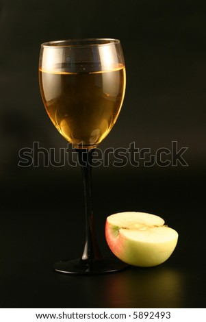 Glass of white wine and an apple on a black background