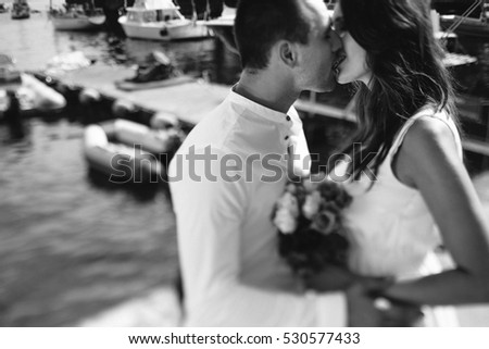 happy groom and bride in white dress hugging sea background
