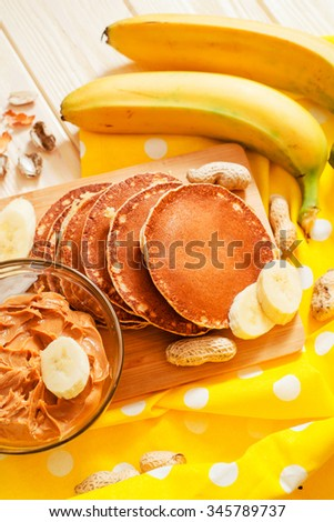 hearty and healthy breakfast , American pancakes with bananas , nuts , peanut butter and milk on a wooden background