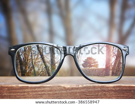 Hipster Glasses On A Park Bench Or Table With A Forest In The Background  Toned With