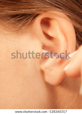 Hygiene concept. Woman cleaning ear with cotton swabs closeup