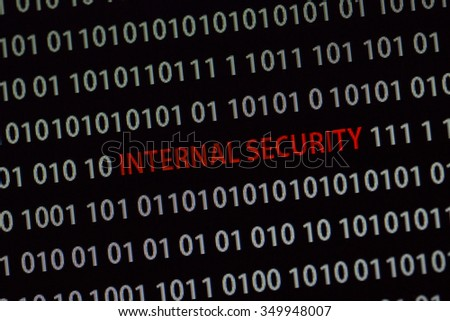 'Internal security' text in the middle of the computer screen surrounded by numbers zero and one. Image is taken in a small angle.