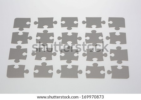 20 jigsaw puzzle pieces placed on illuminated white background.