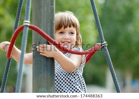 laughing girl climbing at ropes on playground area in summer