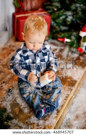 Little baby playing on the floor Christmas decorations. Beautiful interior.Christmas tree