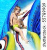 little boy sliding down a water slide  and having fun - stock photo