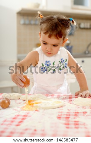 little girl playing with dough and eggs on the kitchen table