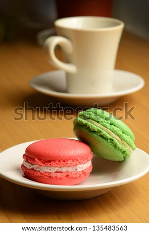 macaroons  on plate with a cup of coffee on wooden table