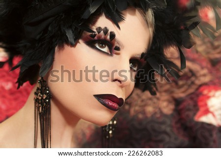 Makeup with feathers on the eyes of the girl in black and red.