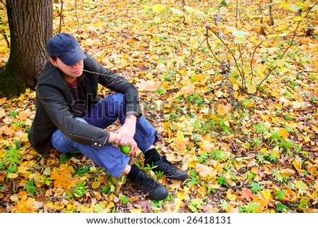 man sitting on the leaves in the forest