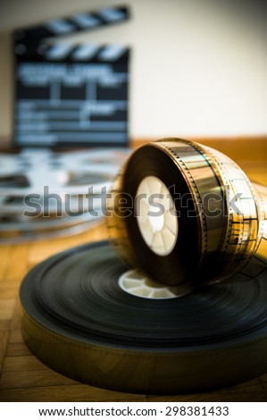 35 mm cinema film reel and out of focus movie clapper board in background on wooden floor vertical frame