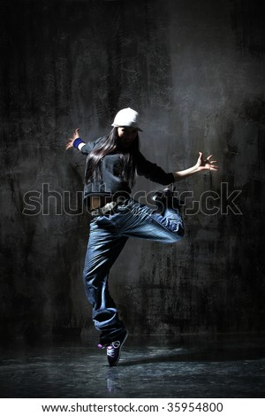 modern dancer poses in front of the old dirty wall