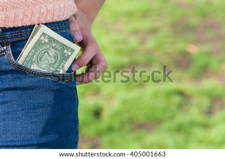 Money in women pocket in the park