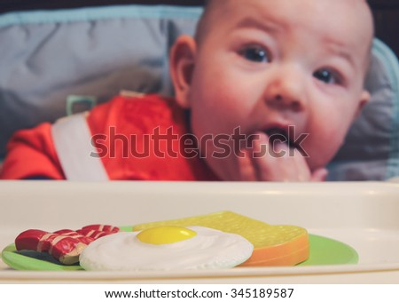 6 month old baby boy sitting in his high chair with a plate of pretend breakfast. Focus on breakfast plate.