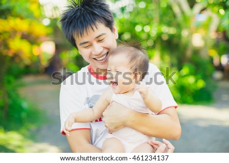 9 months baby laugh and big smile with her father in the garden. An emotional portrait of happy people : Selective focus picture.