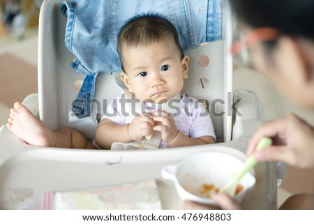 7 months old Asian baby eating fruit for the first time