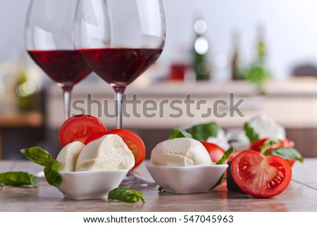 mozzarella with tomato and basil on a kitchen table