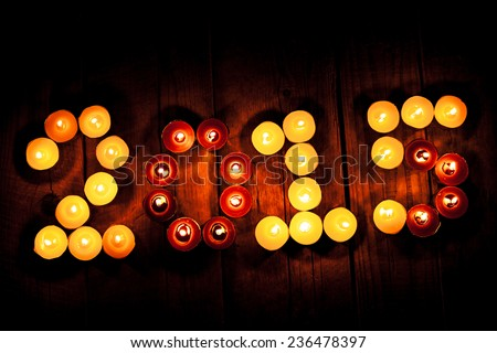 2015 new year. Many beautiful small candle on an old wooden vintage background. Burning candles in the form of numbers