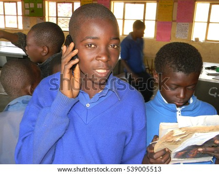 Norton,Zimbabwe,July 20 2015.  Standing  primary  school boy  speaking  on cellphone  speaking  on  cellphone  whilst  his  classmate  read  some a book.
