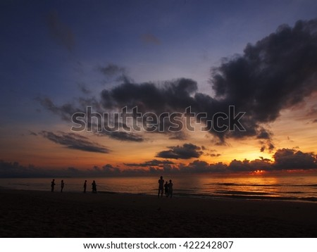 People strolling along one of the beaches at sunset.
