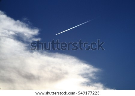 Plane flies in the blue sky leaving a white strip beside the clouds