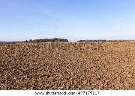 plowed for sowing new crop land is brown in color, photographed closeup, blue sky