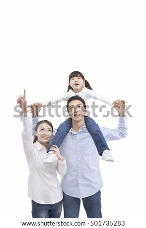 Portrait of daughter riding father's neck,looking up with parents,pointing